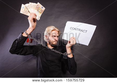 Stress at work no freedom pursuit of money concept. Furious man with chained hands choosing between money and contract studio shot on dark grunge background