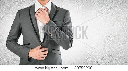 business man hand holding necktie in grey suite on concrete cbackground. smart guy