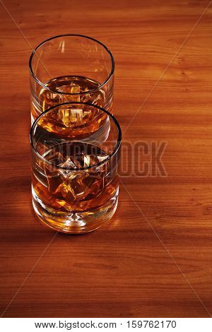 Highball whiskey glass with ice on wooden background. Closeup.