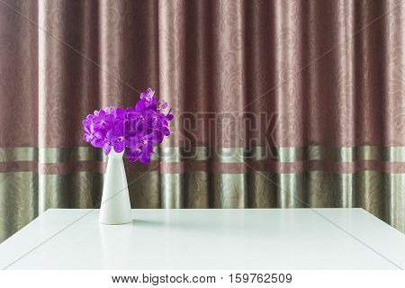 Flowers in a vase on table with certain background.