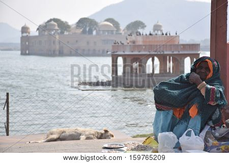 JAIPUR, RAJASTHAN, INDIA - FEBRUARY 05, 2016 - Old indian woman sits on the street with the lake Palace in the background