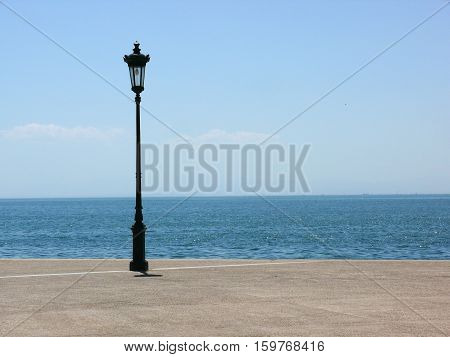 Lamppost on a quay platform by the sea in a Mediterranean city