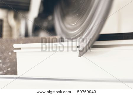 Circular Saw Cutting Pvc Profile Close Up. Plastic Window And Door Industry Production.