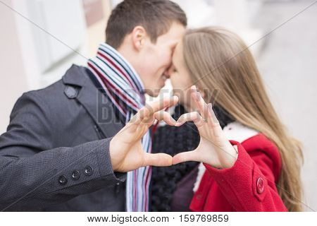Young Couple Making Heart Shape With Hands. Love And Valentines Day Concept.
