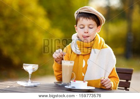 Cute little boy drinking hot chocolate in outdoor cafe on beautiful autumn day