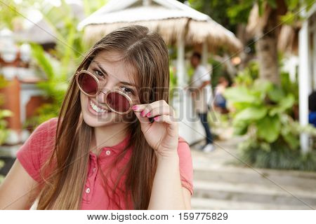Beautiful Lady With Long Loose Hair Taking Off Her Round Sunglasses And Looking At Camera With Happy
