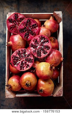 High angle view of ripe red organic pomegranates in crate