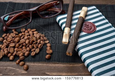 Cigarillos, Cigars, Coffee Beans, Notebook And Glasses On A Bamboo Napkin