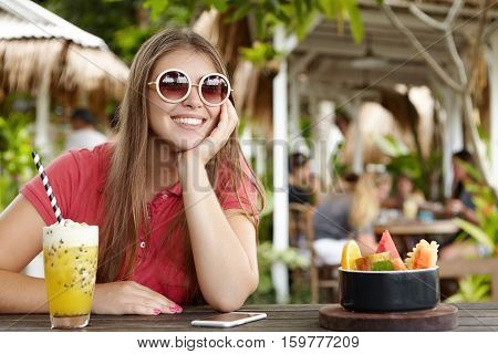 Pretty Woman In Round Sunglasses Enjoying Long-awaited Holiday In Tropical Country, Having Fruit Coc