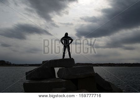 Teen silhouetted on rocks in Scituate on a rock jetty.