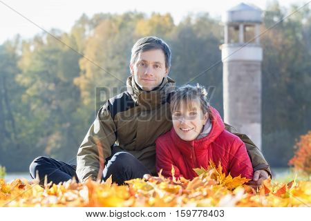 Outdoor family portrait of two young adult people in autumn leaves park background
