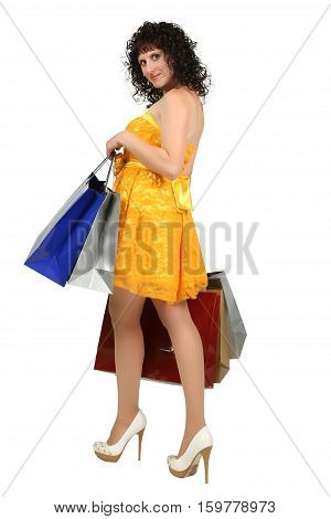 beautiful young brunette in a yellow dress with shopping bags over white