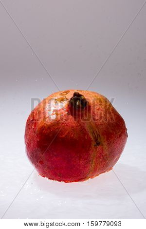 Closeup of whole pomegranate on white with selective focus