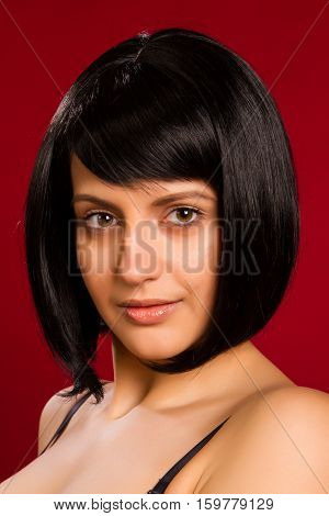 Portrait of sexy brunette on red background in studio