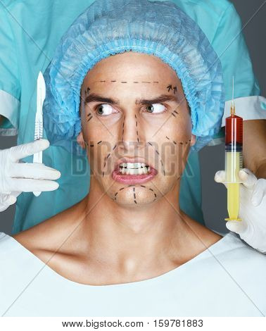 Man patient with horror looks at scalpel. Nurse with syringe and scalpel near the face of scared patient. Close up of male with pencil surgical lines (forehead eyes nose cheekbone and jaw)