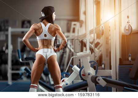 Crossfit woman standing with her back in the gym. Fitness woman, trained body, fitness model. Bodybuilder woman in the gym. Perfect fitness woman sexy buttocks in lingerie. Fitness and bodybuilding