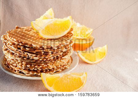Homemade waffles on a plate of orange lobules and around