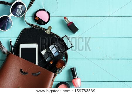 Fashion woman essentials cosmetics cellphone makeup accessories on wooden background Top view