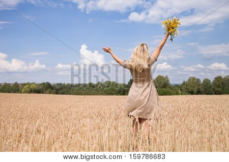 Back view on happy woman with flowers running on the wheat field and enjoying sun. Summer and blue sky background. Girl walking on the meadow. Lifestyle and happiness freedom concept