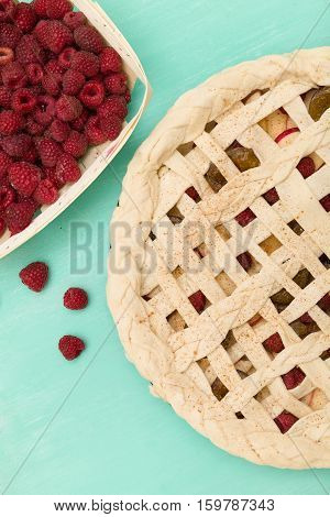 Top view on homemade berry pie with raspberries on turquoise background. dough with berries. Baking at home.