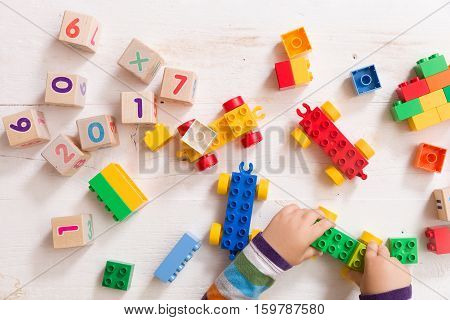 Child playing with wooden cubes with numbers and colorful toy bricks on a white wooden background. Toddler learning numbers. Hand of a child taking toys.