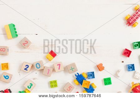 Top view on wooden cubes with numbers and colorful plastic bricks on white wooden table background. School education and learning concept.