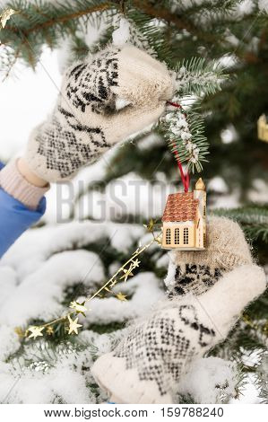 woman decorating Christmas tree outdoors. Closeup of hands in mittens with Christmas decor. Christmas and winter concept.