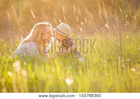 Portrait of young woman hugging her little toddler son on a sunny meadow. Happy mom with her child walking in the park on a sunny day. Mum with boy on sunset. Motherhood and lifestyle concept.