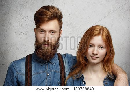 Two Stylish Best Friends Posing Indoors. Fashionable Bearded Caucasian Male Student Embracing Pretty