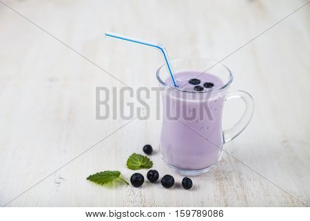 Smoothie Or Yogurt With Blueberries On A Wooden Table. Delicious Milk Drink With Ripe Berries.