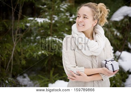 Portrait of young smiling woman holding a nice Christmas present in her hands. Outdoors. Celebration. Holidays gifts and winter concept.
