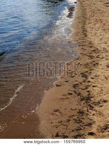 The sandy bank of the river with the oncoming wave, summer day