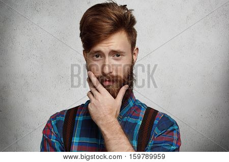 Studio Portrait Of Fashionable Bearded Man Wearing Flannel Shirt And Suspenders Having Doubtful And
