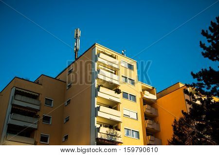 Multi-family house in Munich yellow facade blue sky Antenna for mobile radio on the roof