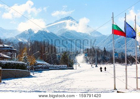 Winter ski resort background with white snow mountain peak, bulgarian flag and snow canons in Bansko, Bulgaria