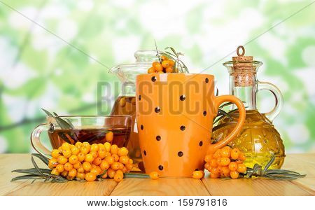 Sea Buckthorn tea, butter and berries on a green background