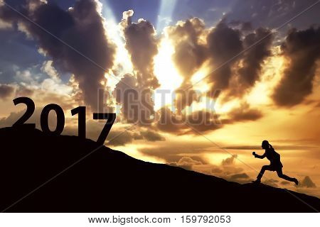 Image of silhouette woman running on the hill toward 2017