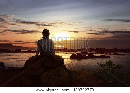 Image of woman sitting on the rock looking the sunset