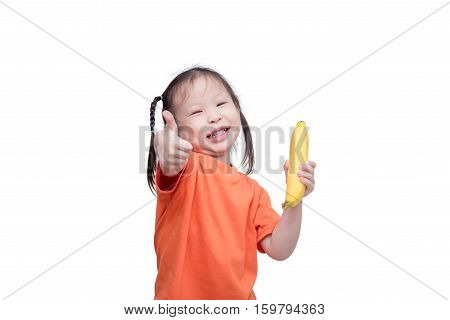 Little asian girl holding banana and showing thumb up