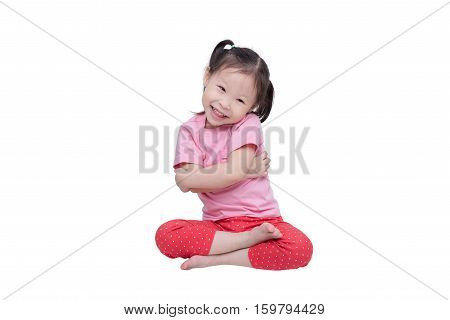 Little asian girl sitting over white background