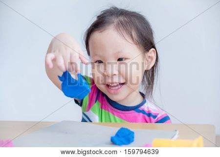 Little asian girl playing with dough on table