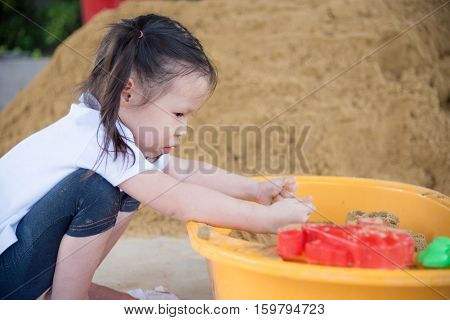 Young asian girl playing sand in sandbox