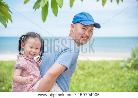 Little asian girl with her father in the garden