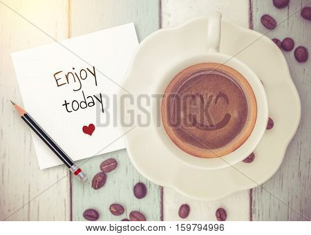 Text :Enjoy today on paper with coffee cup on wood background