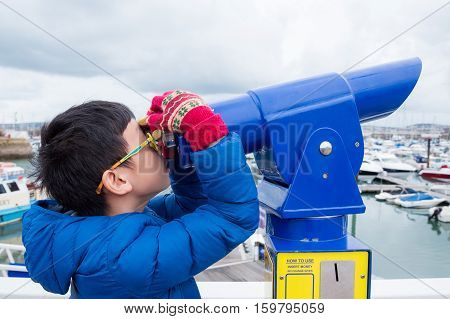 Young asian boy looking in telescope at harbor