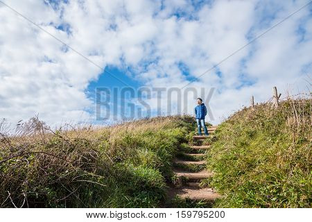 Young asian boy standing on stair with grass field and sky