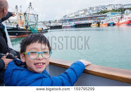 Young happy asian boy smiling on the ship