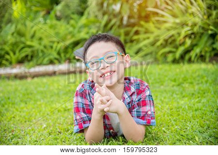 Young asian boy lying on grass field and smiles