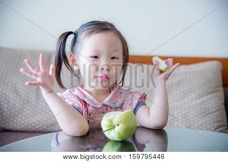 Little asian girl eating guava fruit at home