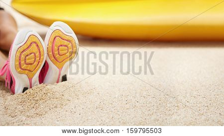 Close Up View Of Female Running Shoes. Athletic Girl Wearing Pink Sneakers Sitting On Sandy Beach Ne